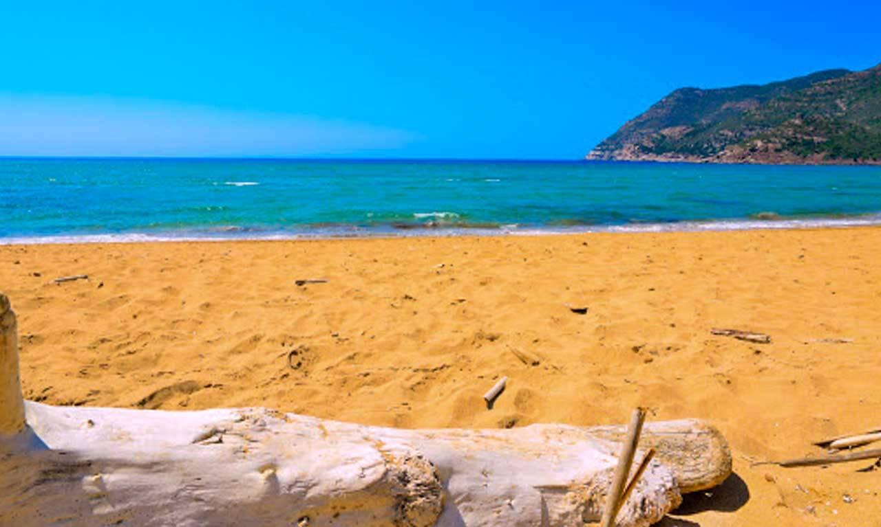 Praia de areia laranja em Porto-Ferro na Sardenha.