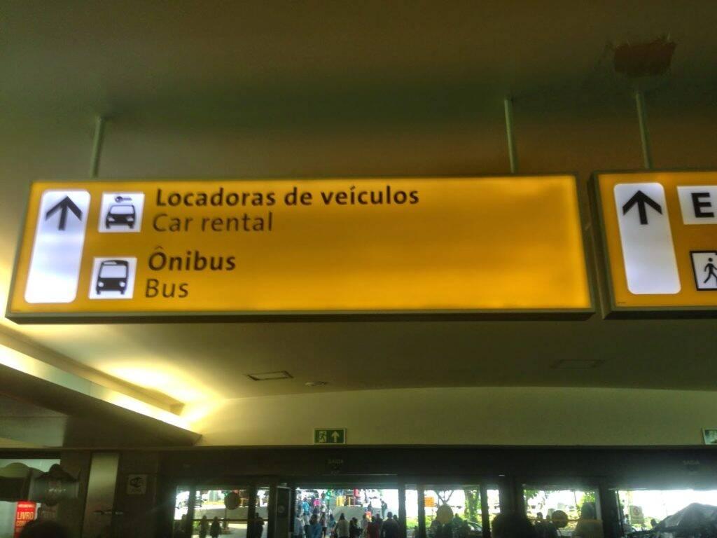 Placa indicando as locadoras de carro e onde pegar o ônibus no aeroporto de guarulhos para sair do aeroporto até o metrô tatuapé