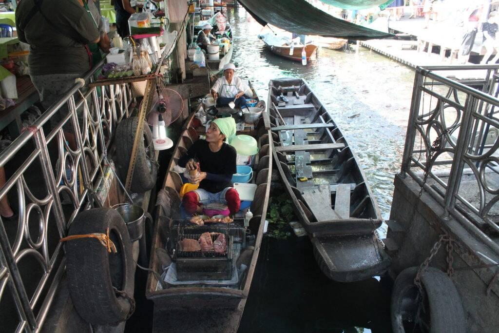 Tailandês assando peixe em um dos barcos do canal do Taling Chan