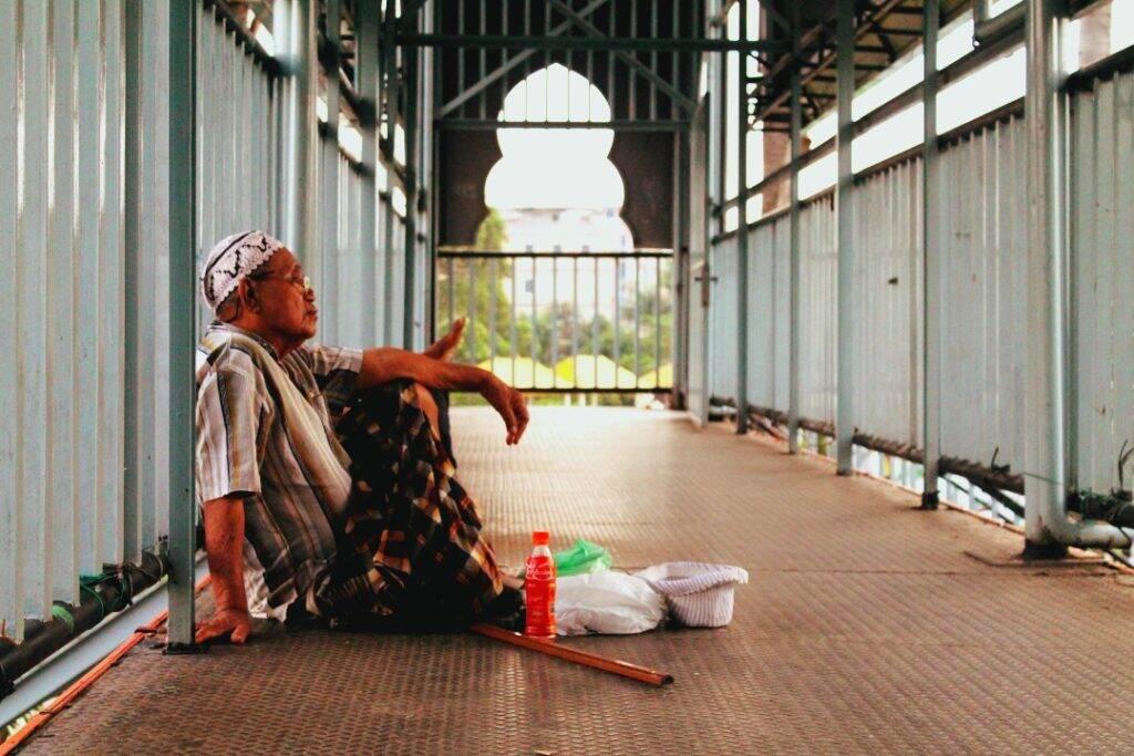 Homem sentado próximo a Grande Mesquita de Medan - dez imagens