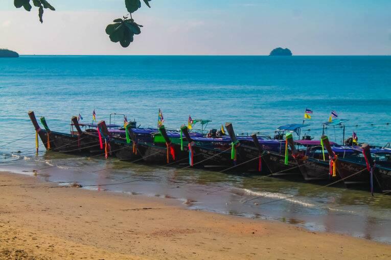 Longtail boats esperando passageiros na praia de Ao Nang, na Tailândia. Foto de: Bruno/@naproadavida