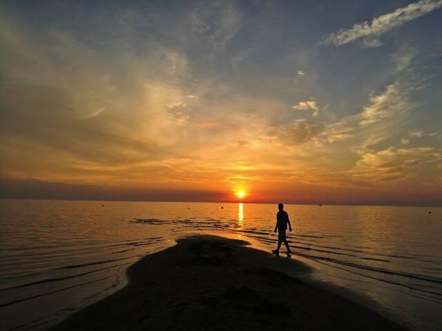 Pôr do Sol maravilhoso de uma praia perto de Riga, na Letônia.