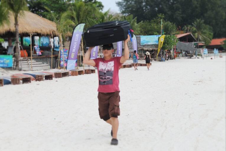 Carregando as malas na cabeça ao descer do ferry em Koh Lipe.