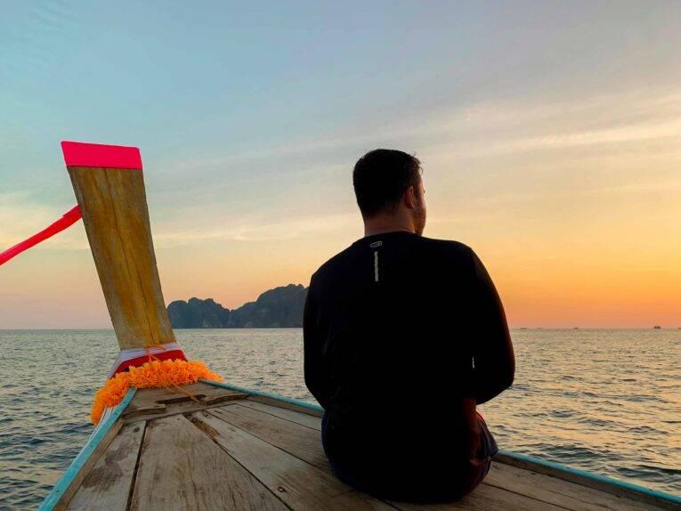 João Pedro num barquinho típico da Tailândia, o longtail boat viajando sozinho