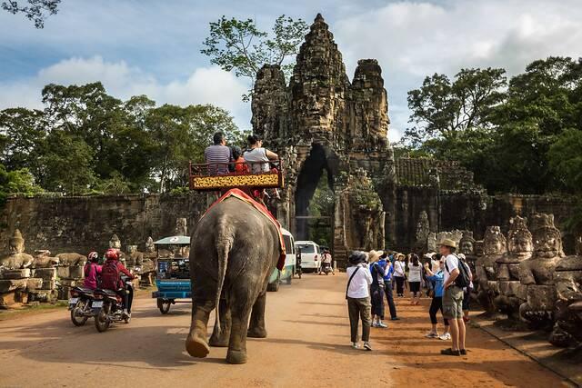Turistas montados em elefante no complexo de Angkor, em Siem Reap.