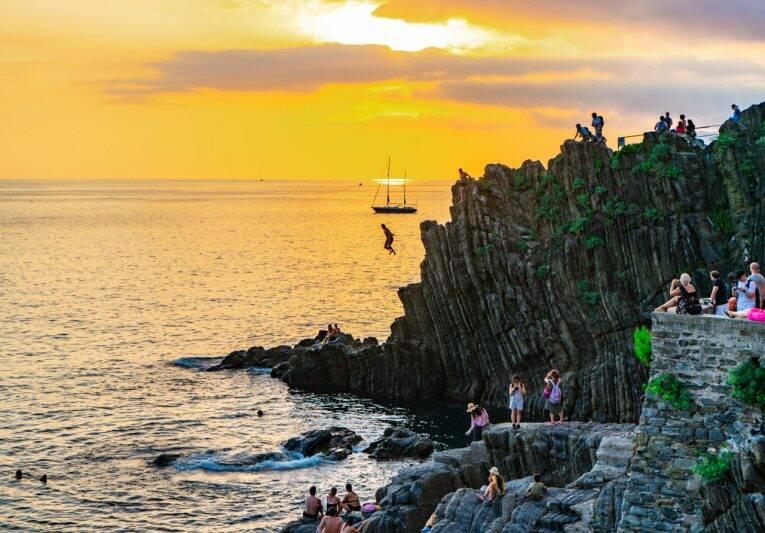 Homem pulando das rochas em Riomaggiore, Cinque Terre.   Foto: Bruno/@naproadavida - seguro viagem para a Itália