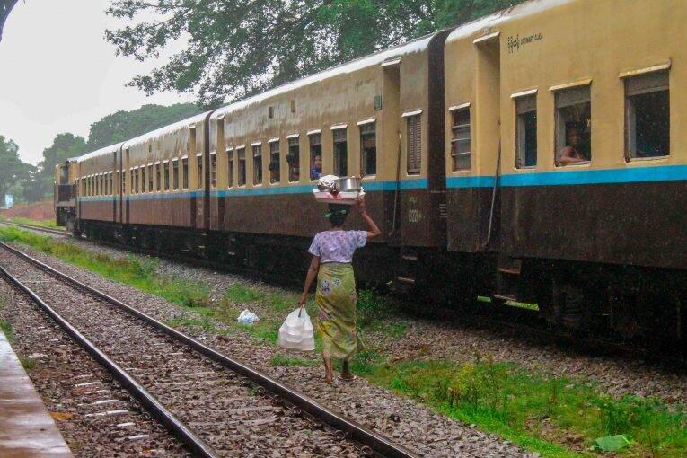 Senhoras birmanesas entram nos trens da Birmânia para vender coisas em cada parada.