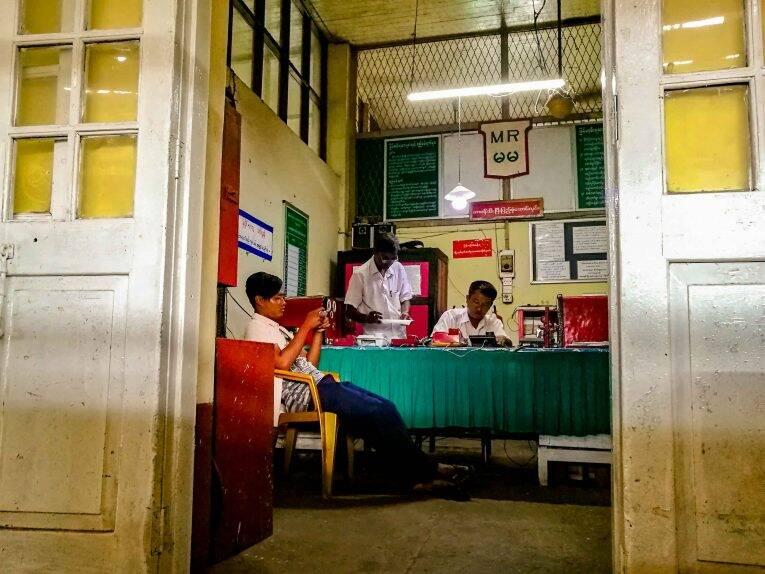 Escritório de uma estação de trem no Myanmar. Homens trabalham na burocracia e papelada.