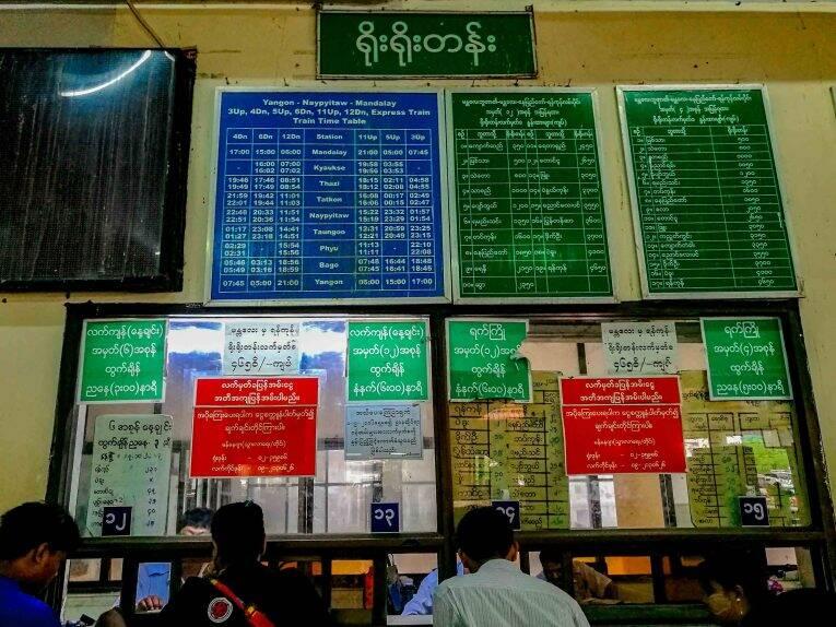 Os guichês e as placas com informações de horário dos trens no Myanmar.