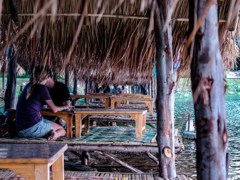 Casal almoçando na beira do Huay Tung Tao Lake.