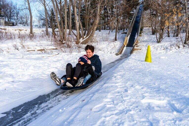 Crianças descendo e se divertindo no tobogã do FortWhyte Alive.