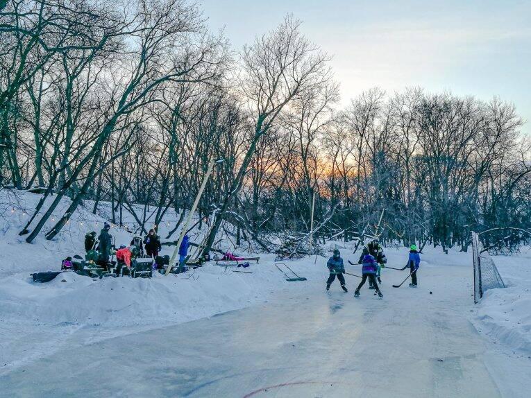 Criançada jogando hockey próximo ao Happyland Park e os córregos congelados.