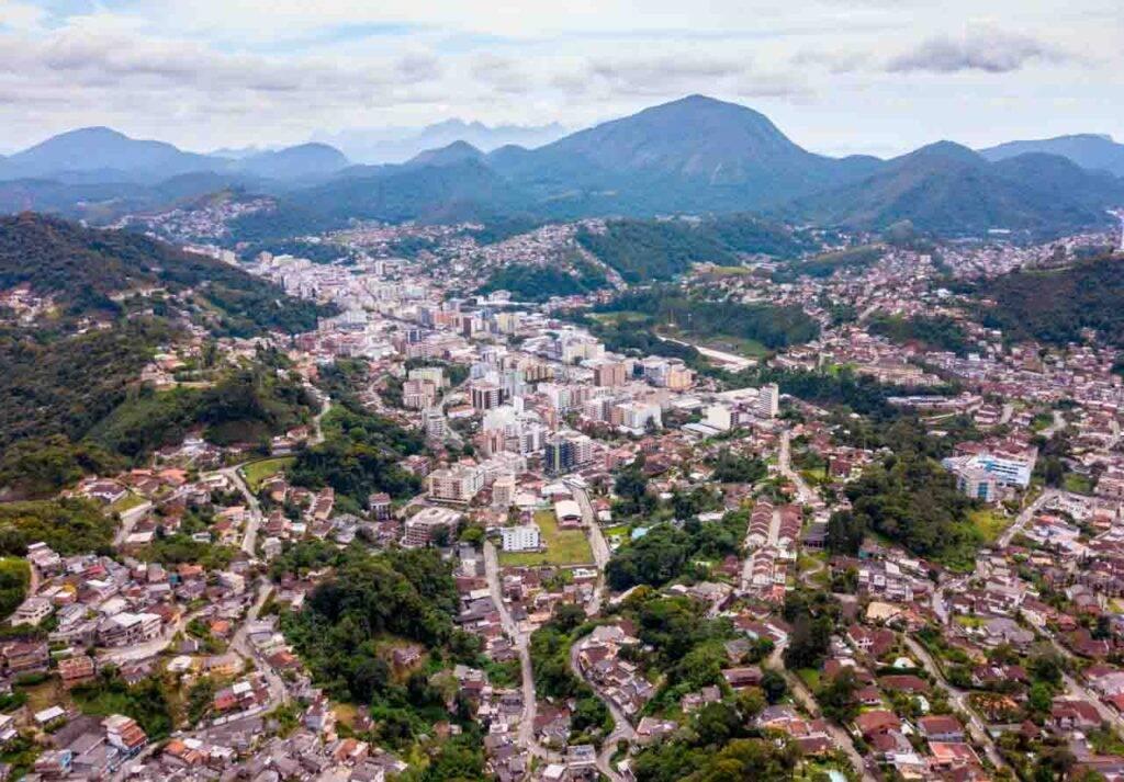 Cidade de Teresópolis vista de cima e as montanhas do Parque dos Três Picos ao fundo. Ônibus SP para Teresópolis