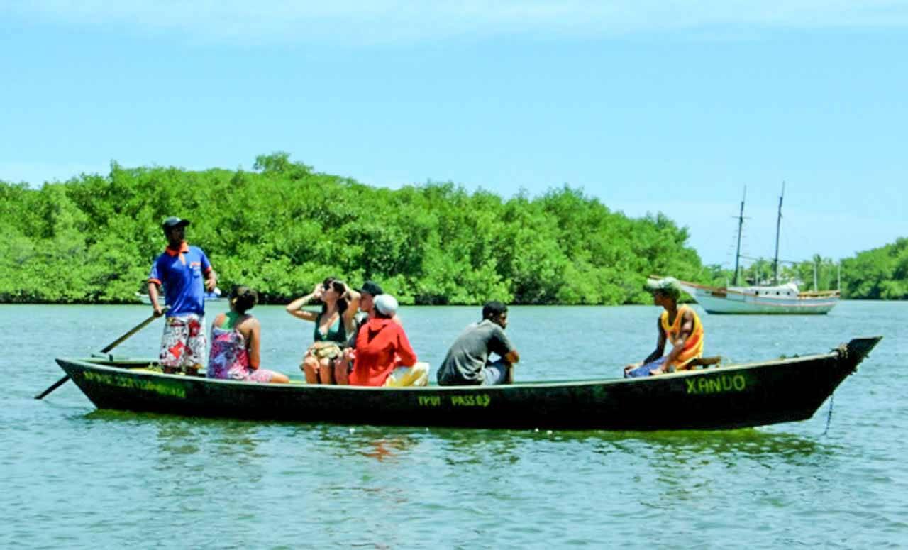 A travessia do portal para chegar em Caraíva na Bahia é feita nessas canoas